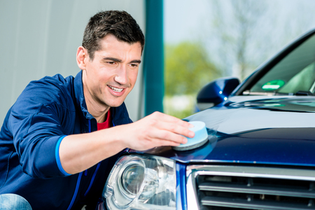 Young man using an absorbent soft towel for drying and polishing the surface of a clean blue car Stock Photo