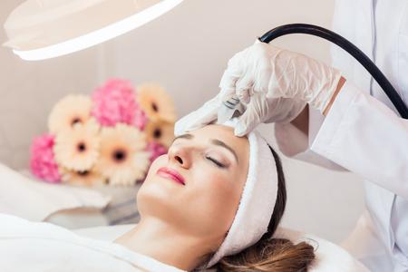 Close-up do rosto de uma mulher bonita sorrindo durante o tratamento facial inovador para rejuvenescimento em um centro de beleza com tecnologia moderna