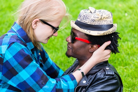 Caucasian woman and African man in loving embrace, looking in each others eyes as a couple
