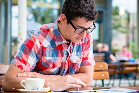 Young man drinking coffee in street cafe and reading the news on tablet device