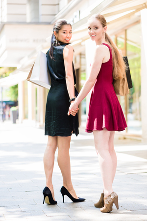 Two happy beautiful women looking at camera while carrying paper bags during shopping session downtown in summer