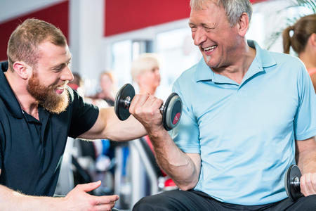 Senior man training with personal trainer at the gym