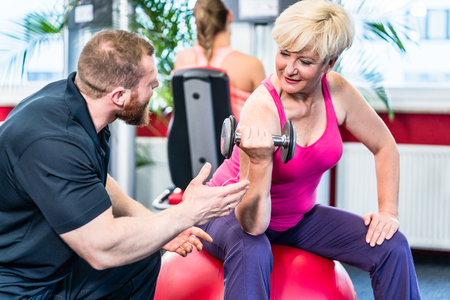 senior woman working out with dumbbells with personal trainer at gym Standard-Bild