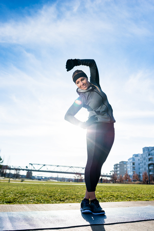 Athletic young woman practicing stretching exercise while standing with crossed legs outdoors in a sunny day in the park