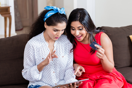 Two young women using a tablet PC for online payment with the credit card Standard-Bild