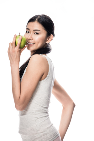 Happy Asian young woman looking at camera while holding a green apple against white background Standard-Bild