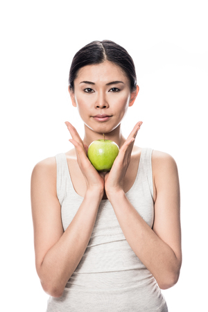 Thoughtful young Asian woman holding a green apple against white background