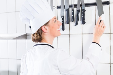 Female chef in uniform in industrial kitchen taking knife from wall bracket