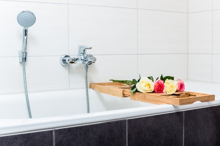 Bathtub with relaxation arrangement of flowers and candles