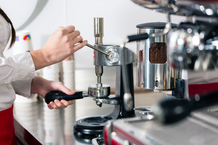 Close-up of the hands of a waiter preparing espresso at an automatic coffee machine Standard-Bild