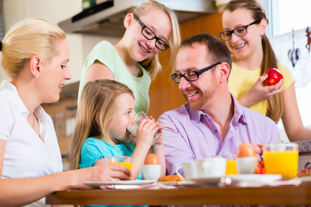 Family in their home having breakfast with eggs, fruit, coffee and juice Standard-Bild