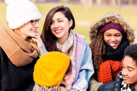 Multi-ethnic group of young people having a good time together outdoors in a cold day Standard-Bild