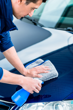 Close-up of male hands cleaning car with spray cleaner and microfiber towel outdoors at car wash