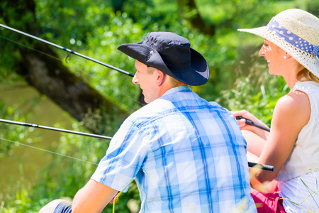 Couple, woman and man, sitting at river side with fishing rods angling for sport Standard-Bild