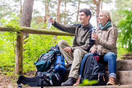 Backpackers hiking and taking rest in the woods and having mineral water Standard-Bild