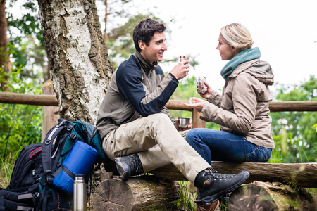 Backpacker couple taking rest aside hiking trail having coffee and sandwiches Standard-Bild