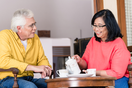 Portrait of serene senior couple looking at camera while enjoying a cup of coffee at home