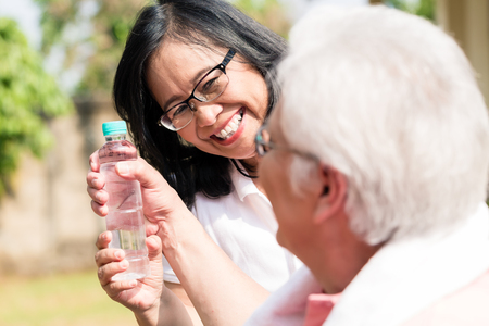 Careful senior woman giving a bottle of water to her partner outdoors in a summer day