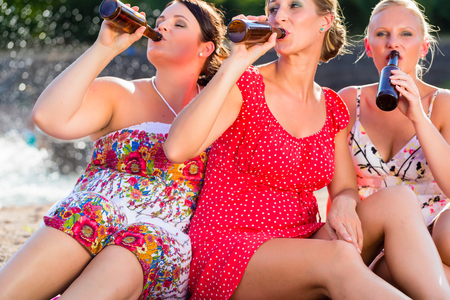 Friends drinking beer together at river beach Banque d'images