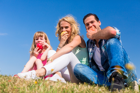 Mommy, daddy and little girl sitting on meadow eating fruit