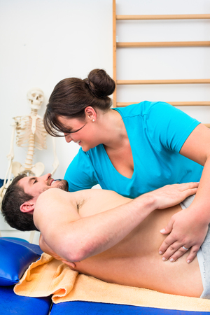 physiotherapist treating young bare-chested man on couch