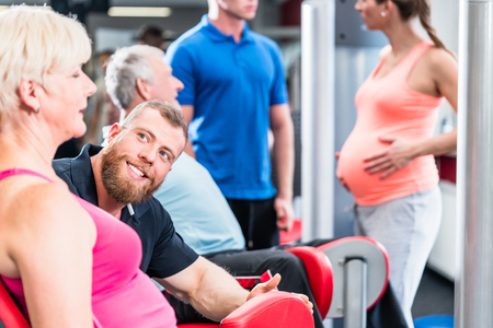 Senior woman with trainer in group with pregnant woman working out at the gym