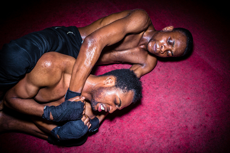 Two African American opponents struggling for dominance in ground fighting during MMA match Standard-Bild