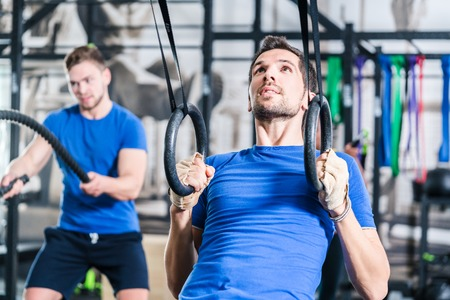 Men at rings doing fitness exercise in gym