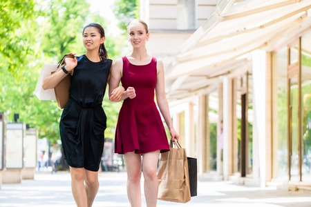 Two fashionable young women carrying paper bags while walking in the city during a relaxing shopping session in summer Standard-Bild