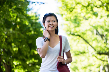 Serene beautiful young woman smiling while walking in the park in summer Standard-Bild