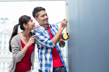 Young indonesian couple, woman and man, doing home improvement in their new residence