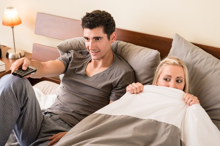 Funny young couple sitting in bed while watching TV together at night