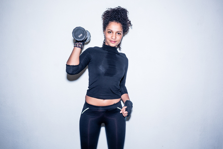 Portrait of young fit woman looking at camera while holding up a 5kg dumbbell