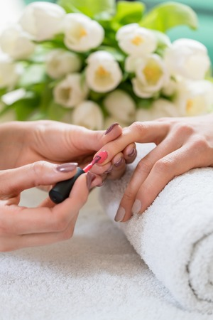 Close-up of the hands of a skilled manicurist, applying elegant red nail polish on the medium length nails of a young woman in a trendy beauty salon