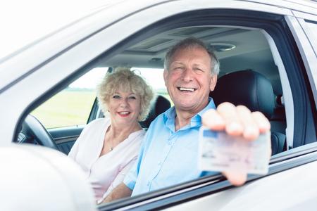 Porträt eines glücklichen älteren Mannes, der seinen verfügbaren Führerschein beim Sitzen im Auto nahe bei seiner netten Frau zeigt