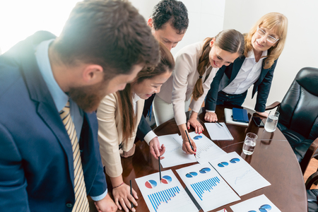 Multi-ethnic team of five dedicated specialists smiling while analyzing various charts with positive statistics about the profit and the development of the company Stock Photo