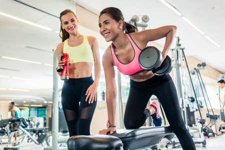 Low-angle view portrait of a determined and powerful young woman, smiling and holding a dumbbell while rowing with one arm in a trendy health club Stock Photo