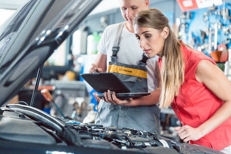 Reliable auto mechanic showing to a female customer the engine error codes scanned by a car diagnostic software in a modern automobile repair shop