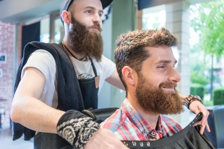 Side view of a handsome young bearded man smiling before having a trendy haircut done by his trustworthy barber in a hair salon for men