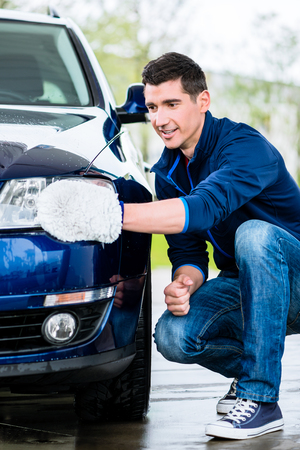 Proud car owner cleaning the headlamps of his luxury sedan with a soft absorbent mitt Stock Photo