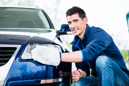 Smiling man cleaning the headlamp on his car wiping it with a mitt as he crouches alongside the vehicle
