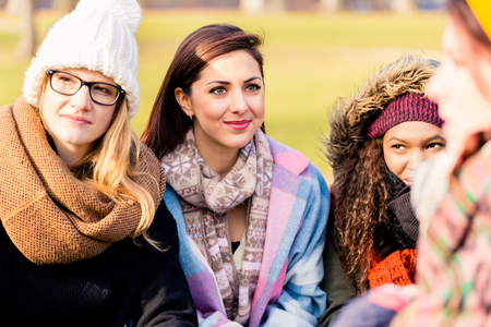 Confident young women daydreaming while sharing ideas and future plans outdoors