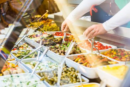 Femme vendant des amuse-gueule Meze dans une épicerie fine