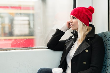 Young Woman looking out of train window using phone