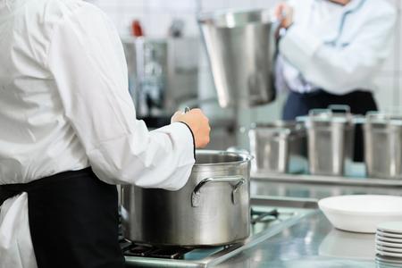 Szefowie kuchni przy piecu w profesjonalnej kuchni cateringowej mieszając w garnkach