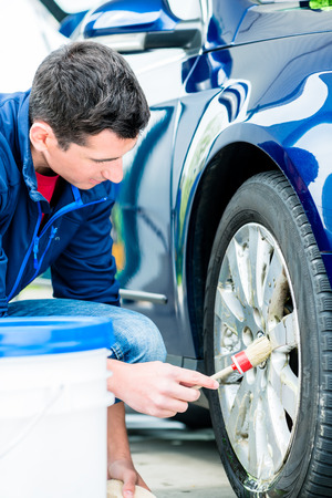 Young man using brush for cleaning the surface of the rim of a blue car at auto wash Stock Photo