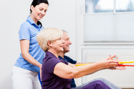 Physio instructing senior man and woman during gymnastic exercise