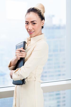 Asian businesswoman in front of skyscraper window in office