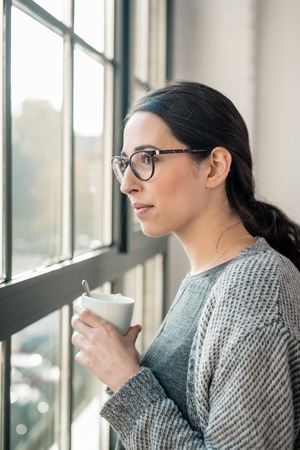 Young pensive woman with serious facial expression looking through the window during break at work