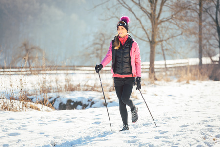 Woman on the trail for a winter hike in sunny landscape